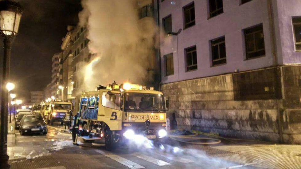 Actuación de los bomberos en el incendio del bazar chino de Sotrondio.Un bombero ante uno de los enseres afectados por el incendio en El Castrillón (Laviana)