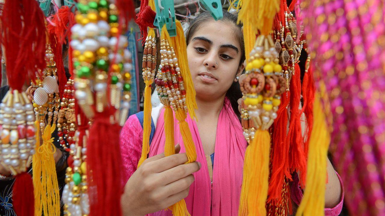 Una mujer india observa los collares de una tienda durante el festival Raksha Bandhan
