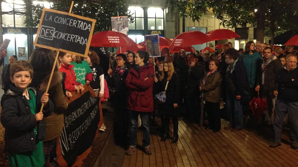 Auxiliares educativos y fisioterapeutas en la Consejería de Educación entregando las más de 4.000 firmas recogidas.Un momento de la «paraguada» por la escuela pública en Gijón