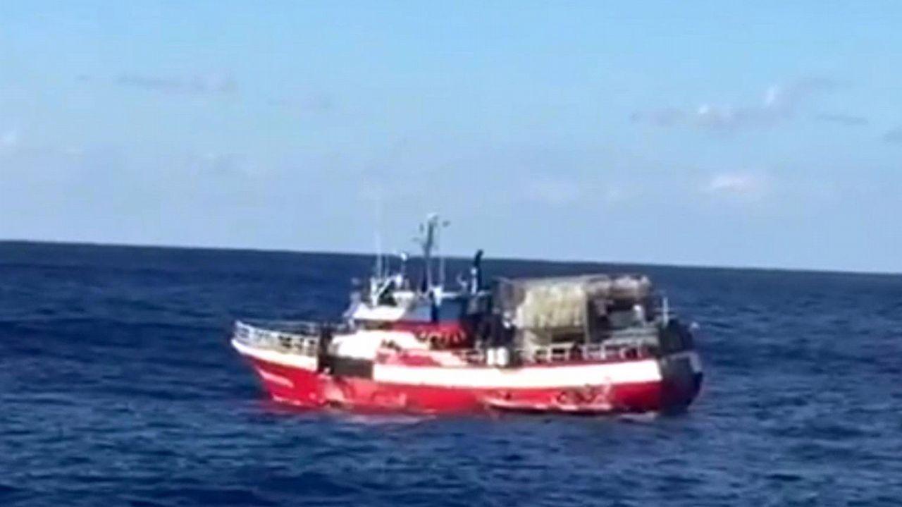 Un policía y un guardia civil saludan a uno de los 137 menores que llegaron a Algeciras en el barco de Open Arms