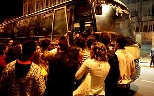 .Un grupo de jóvenes hacen cola ante un bus nocturno, en una imagen de archivo