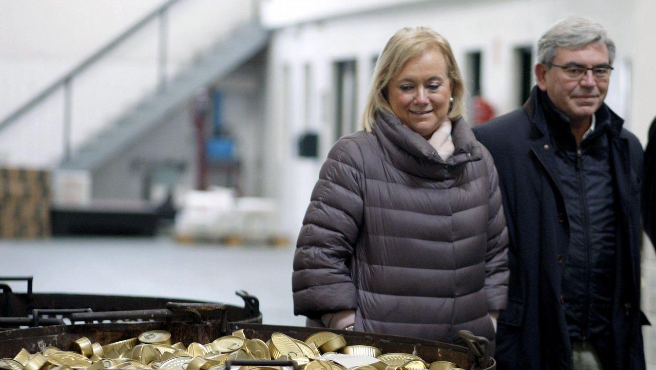 La presidenta del PP de Asturias, Mercedes Fernández (i) acompañada por el presidente del PP de Gijón, Mariano Marín (d) durante la visita que ha realizado hoy a una fábrica de conservas de Gijón
