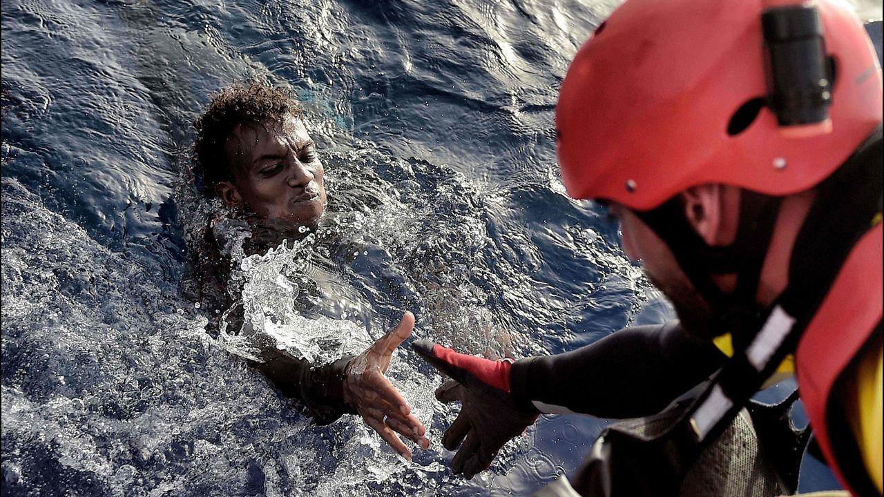 .Un activista de Proactiva Open Arms auxilia a un migrante en aguas del Mediterráneo