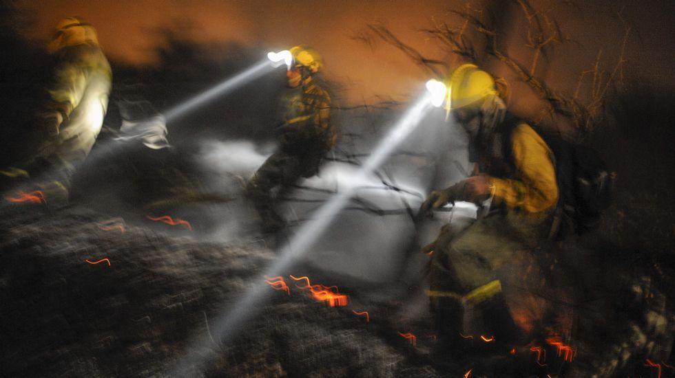Tres brigadistas intetan extinguir el fuego