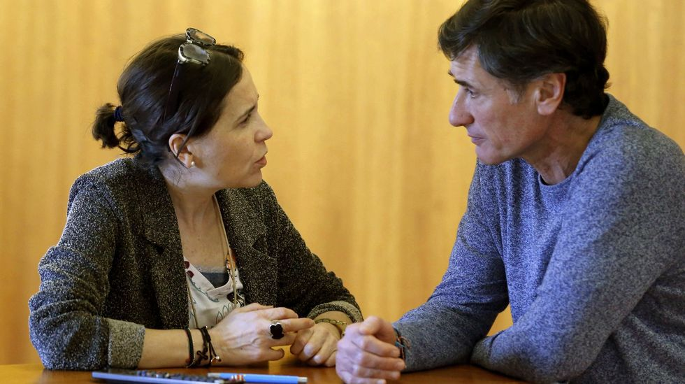 .La consejera de Hacienda, Dolores Carcedo (i), y el diputado de Podemos, Enrique López (d), conversan durante el pleno de hoy de la Junta General del Principado