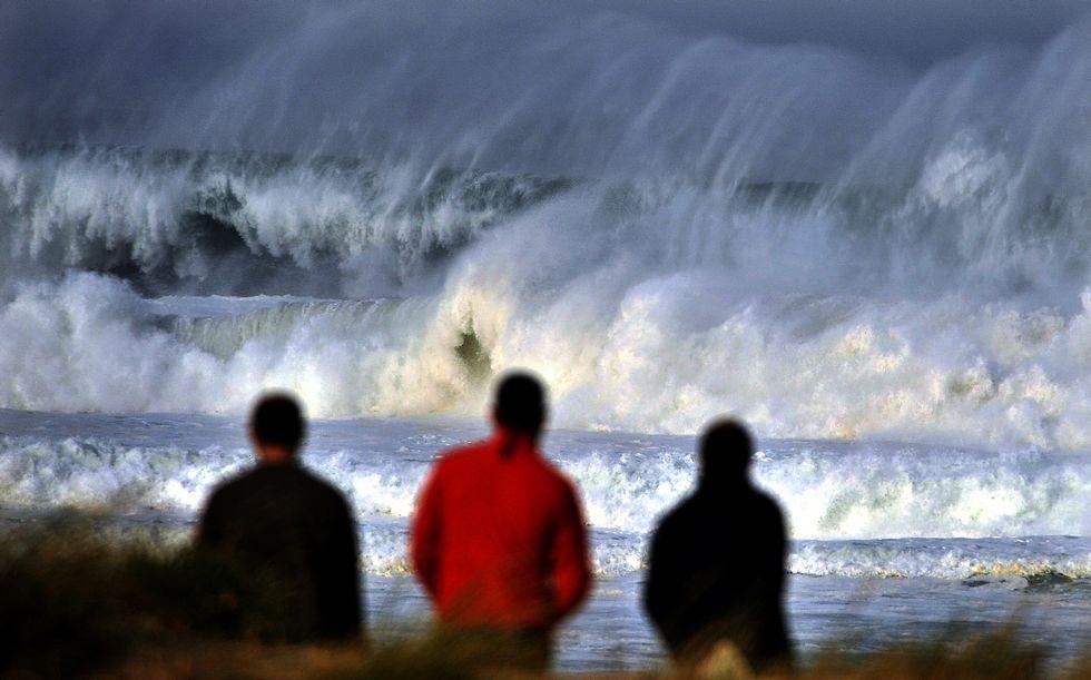 Tres vecinos observan el fuerte oleaje, en foto de archivo.