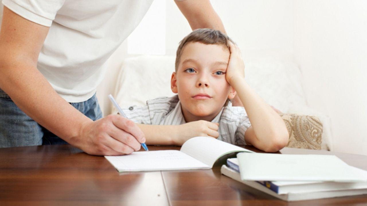 Niño haciendo deberes y padre ayudándole.Carlos López Otín