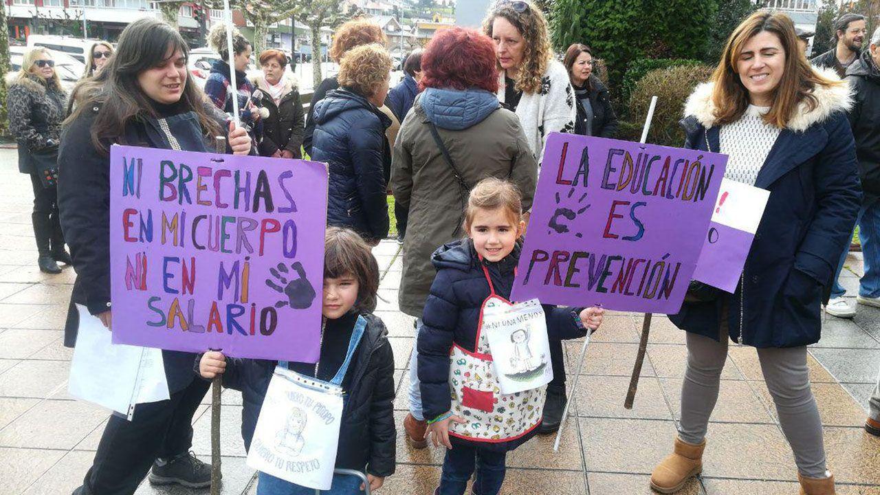 Registro en la casa del detenido por la muerte de Paz Fernández.Dos niñas posan ataviadas con los eslóganes del 8M, en la concentración en Castrillón