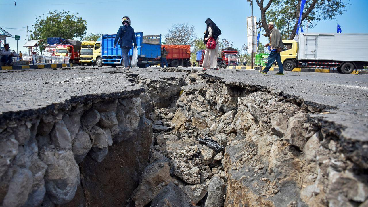 La gente camina cerca de una gran grieta de una carretera formada por el gran terremoto que tuvo lugar ayer en Indonesia.