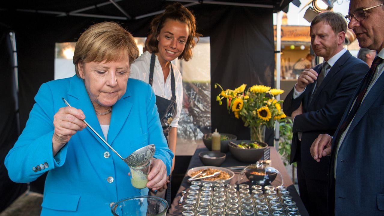 Canciller alemana Angela Merkel llena un vaso con sopa de pepino en un puesto durante la fiesta de verano del grupo parlamentario CDU en Dresden