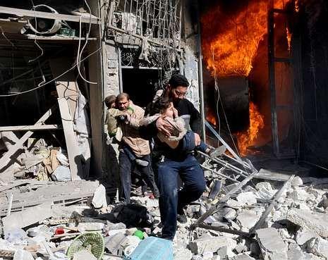 Dos hombres evacúan a dos niños en un edifico alcanzado por barriles bomba en Alepo.
