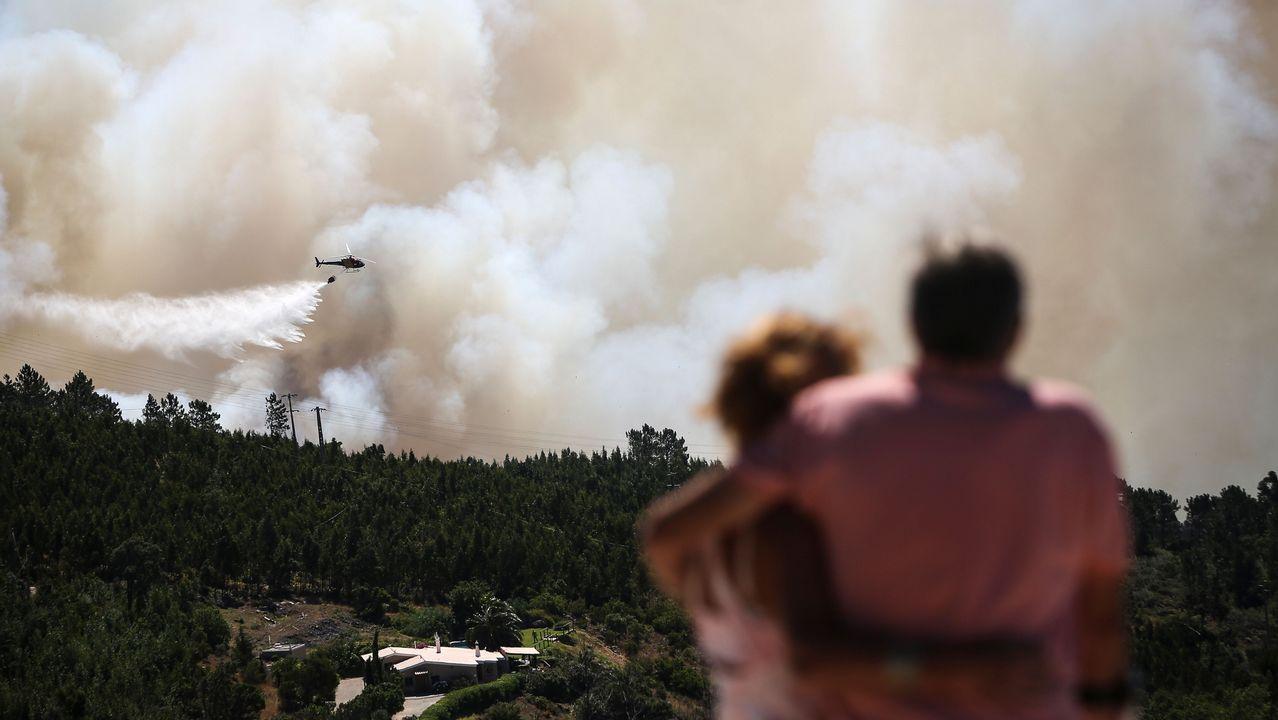 Una pareja observa el trabajo del helicóptero