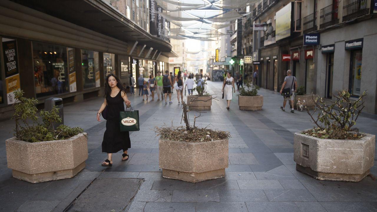.Viandantes caminan por la Calle Preciados de Madrid, una de las vías comerciales más concurridas de la capital, donde hoy se han colocado jardineras para evitar el tránsito de vehículos después de los atentados ocurridos
