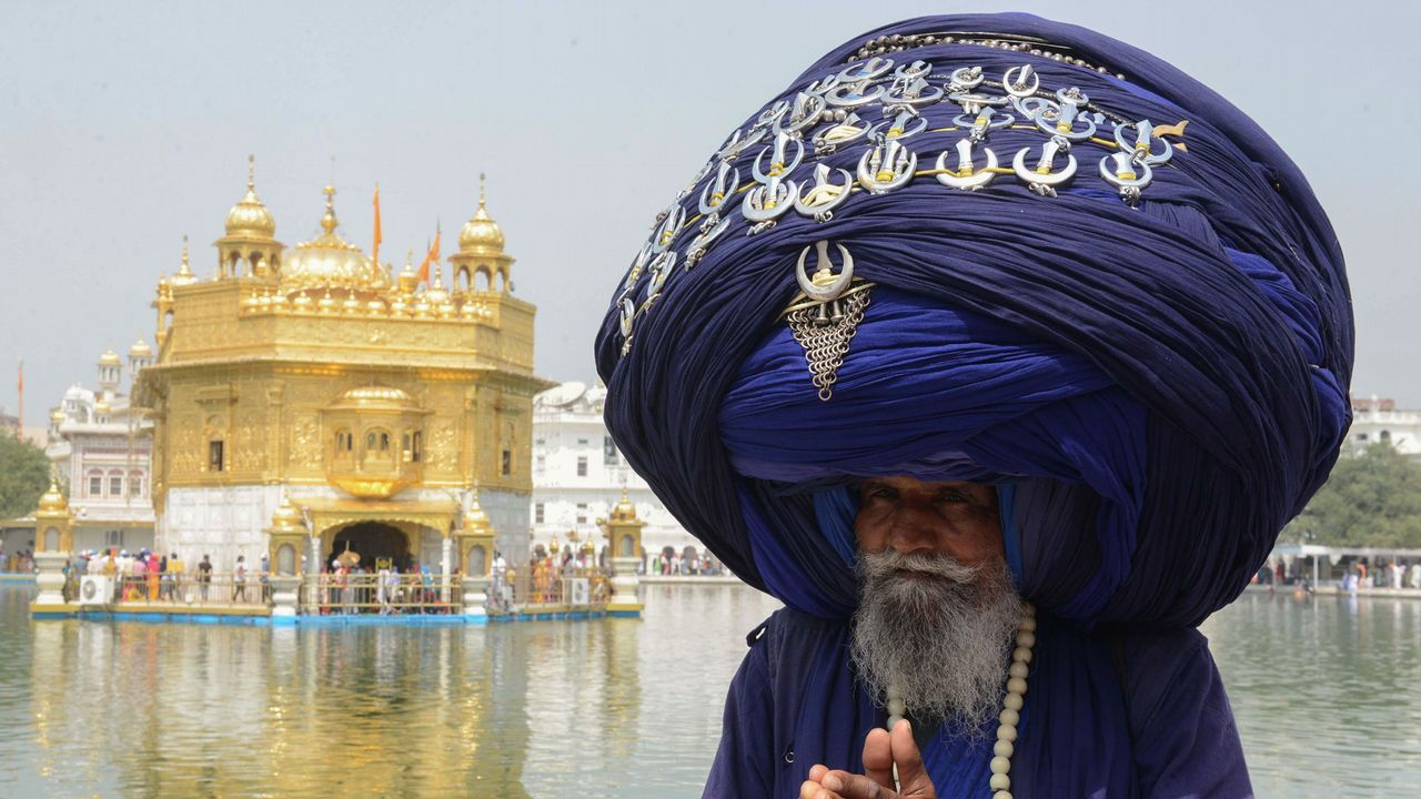 Un religioso indio ataviado con un turbante gigante en el Templo de Oro de Amritsar, en India