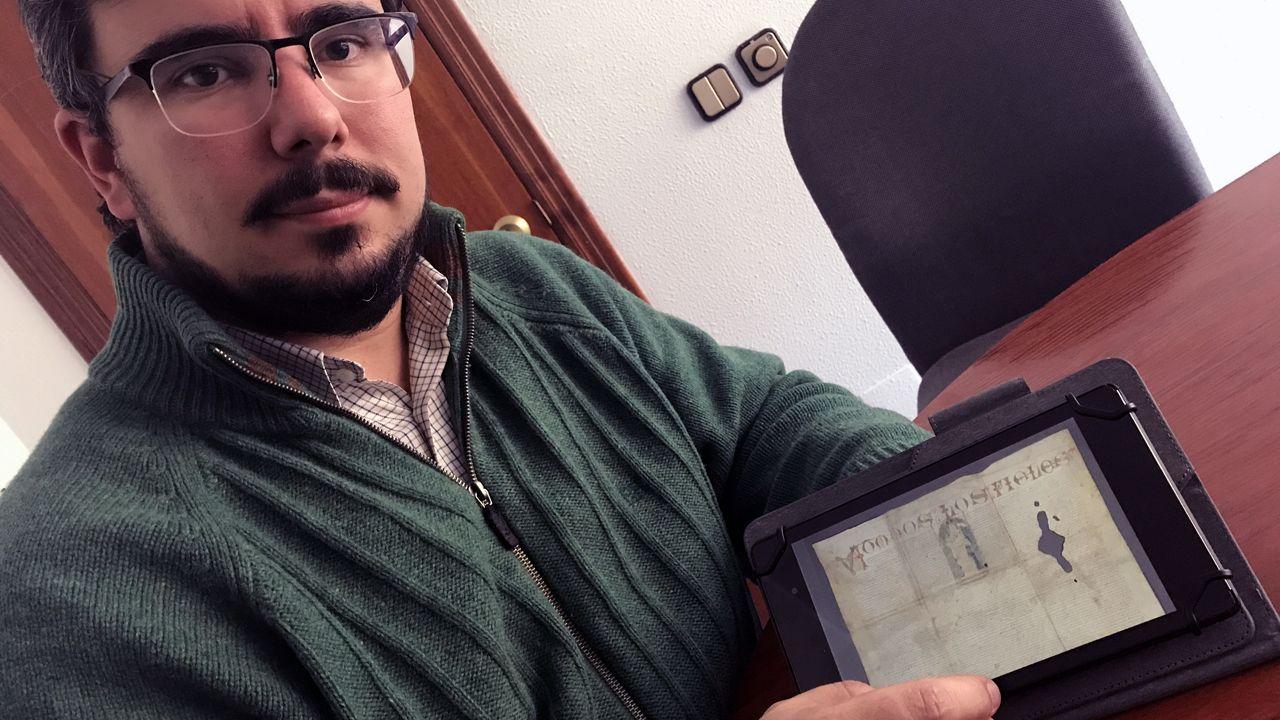 .Álvaro Solona, medievalista de la Universidad de Oviedo, muestra un cartel vinculado al Camino del Salvador