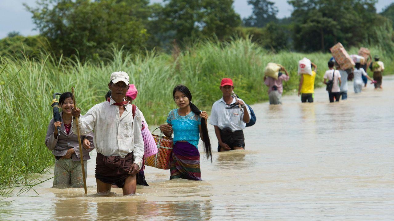 .Varios residentes de aldeas de Myanmar, junto a la región de Bago, intentan salvar sus cosas ante una gran inundación.