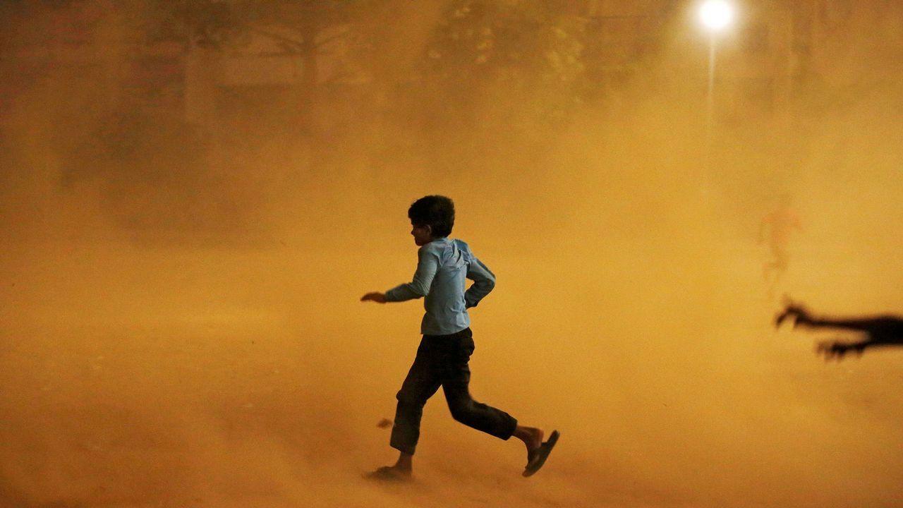 .Un niño corre para protegerse de una tormenta de arena en Nueva Delhi, en India