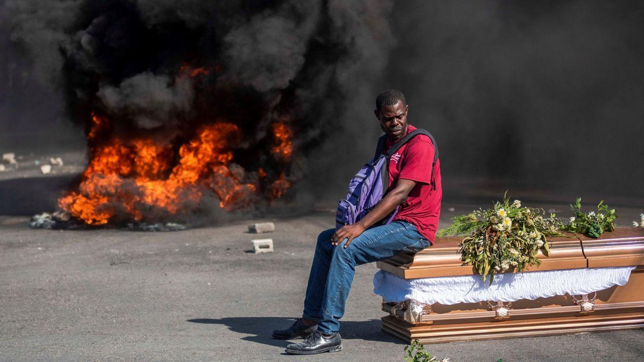 Un hombre permanece sentado sobre el féretro de una de las víctimas de las protestas de febrero contra el Gobierno de Jovenel Moise