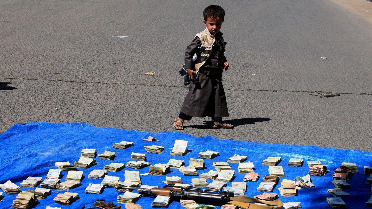 Un niño contempla los donativos de dinero y armas que simpatizantes de los rebeldes hutíes han recogido para destinarlos al frente de Al Hudeida en Saná (Yemen)