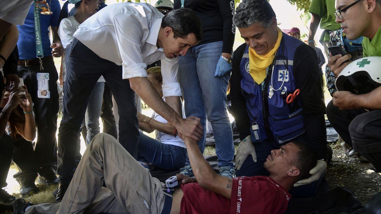 Juan Guaidó saluda a un voluntario que se desmayó durante una manifestación en Caracas