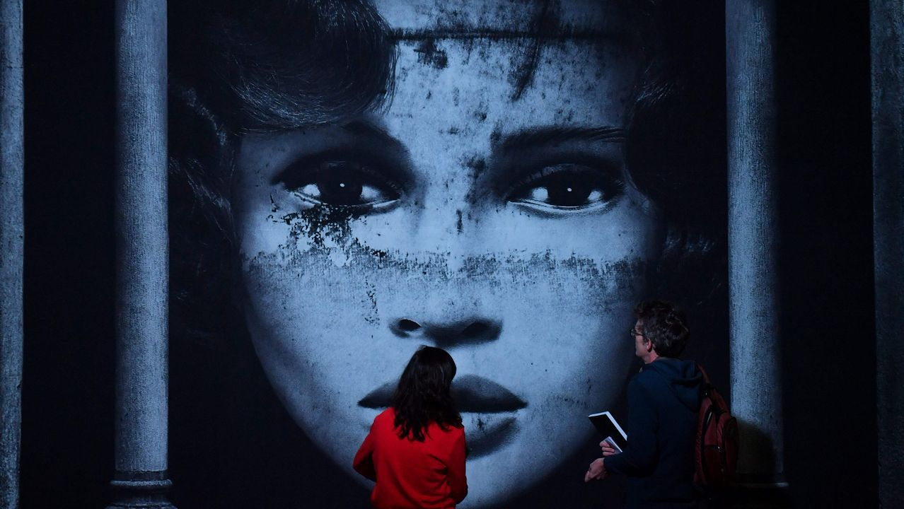 Dos personas observan una de las obras de arte urbano que forma parte de la exposición Srokar Inside, abierta en Bruselas