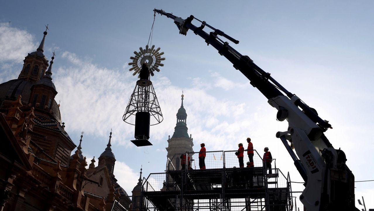 Operarios municipales colocan la imagen de la Virgen del Pilar sobre el andamio, en Zaragoza, en el que se colocarán las flores de la ofrenda del día 12 de octubre