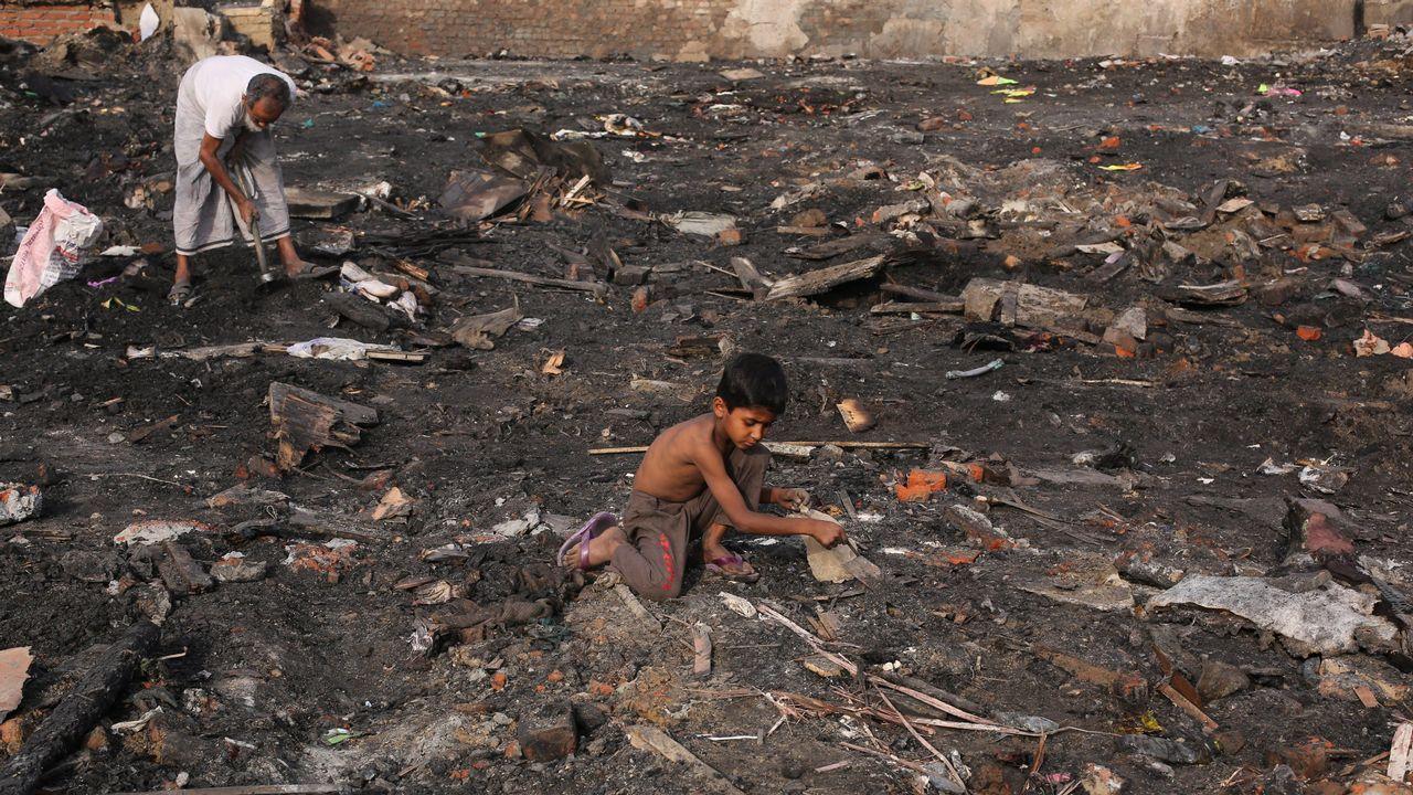.Un niño rohingya busca sus pertenencias entre restos calciandos de un asentamiento temporal en Nueva Dehli