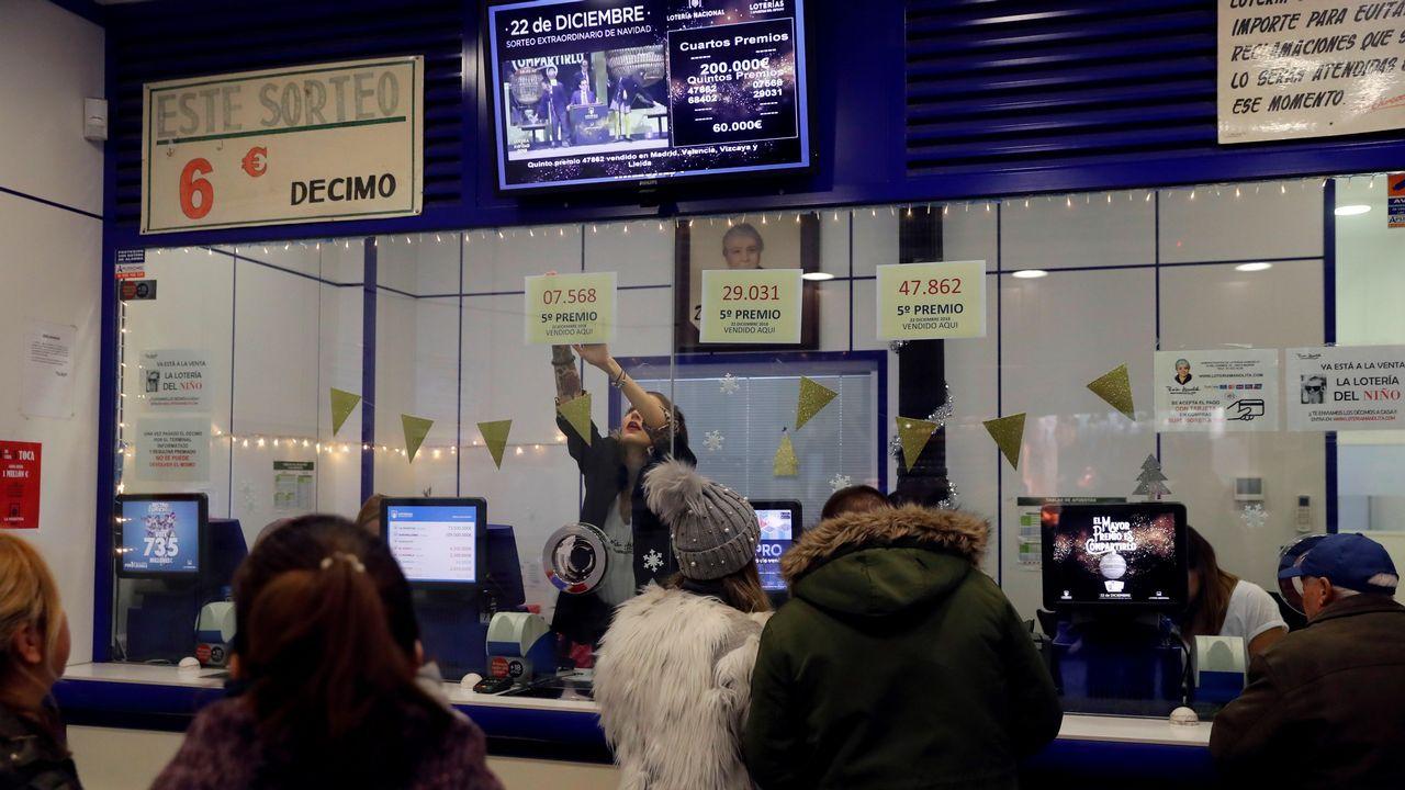 Una empleada de la administración de Loteria de «Doña Manolita» en la madrileña calle Carmen, 22, coloca los números correspondientes a los tres quintos premios del sorteo Extraordinario de la lotería Navidad dotado con 60.000 euros a la serie cada uno, que ha vendido esta administración.