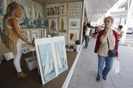 Lleno en María Pita para ver a Marta Sánchez.Pilar Fandiño en su puesto de la Feria de Artes Plásticas