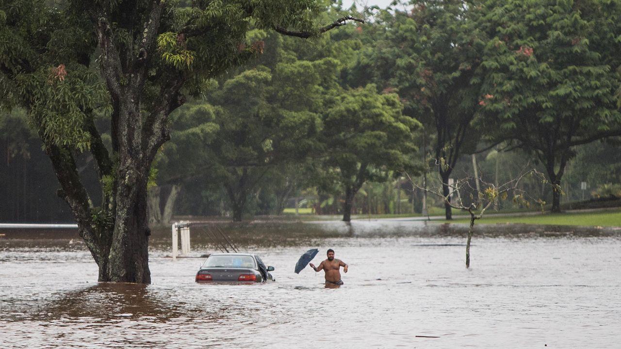 El propietario de un coche, prácticamente sumergido, intenta rescatar objetos personales de su interior, en una avenida afectada por las inundaciones provocadas por el paso del huracán Lane en Hilo, Hawái