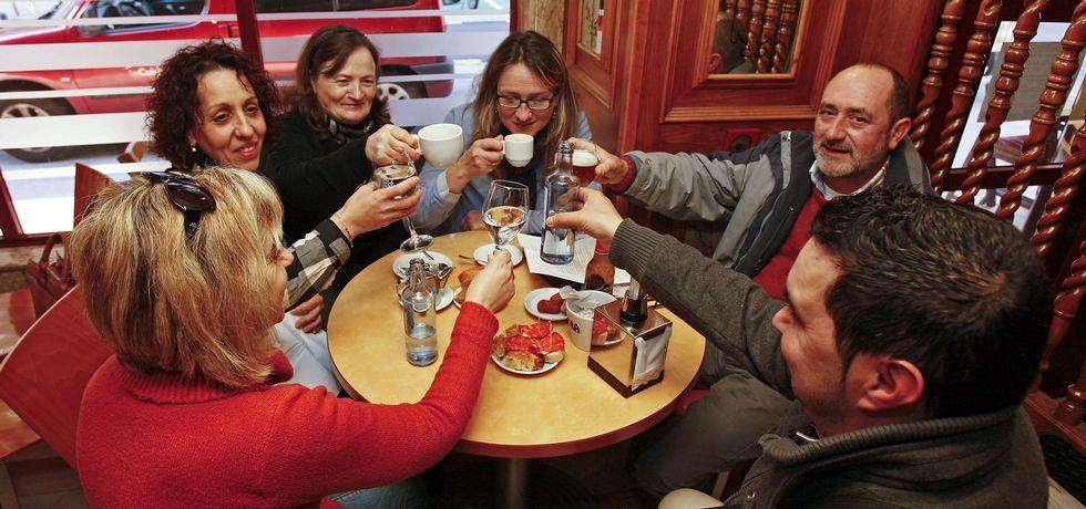 Celia, Amalia, Milagros, Isabel, José y Carlos (de iz a dcha), ayer, celebrando al calor de un café que no pasarán más frío en sus quioscos.