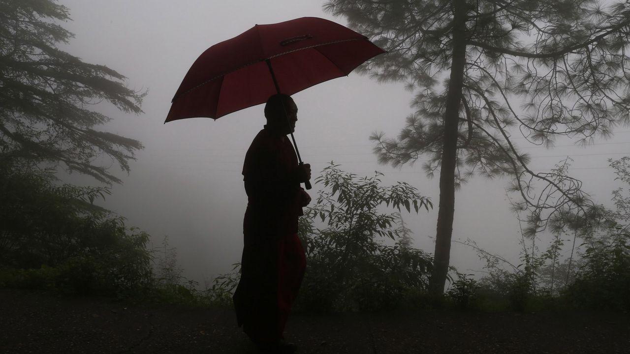 Un tibetano exiliado en la India camina bajo la lluvia durante una ola de tormentas monzónicas en McLeod Ganj, cerca de Dharamsala