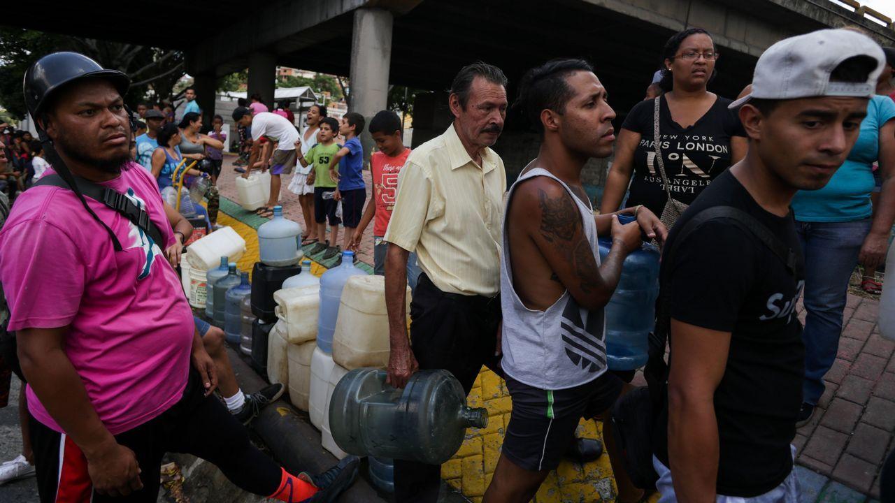 | REUTERS.Vecinos de Caracas hacían largas colas para conseguir agua potable