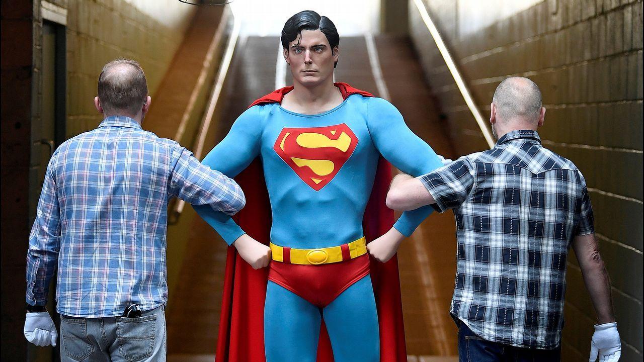 .Dos empleados trasladan, en Londres, una reproducción del Superman encarnado por Christopher Reeve en 1978 y 1980