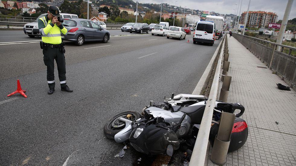 .Un agente fotografía la moto tirada en al suelo