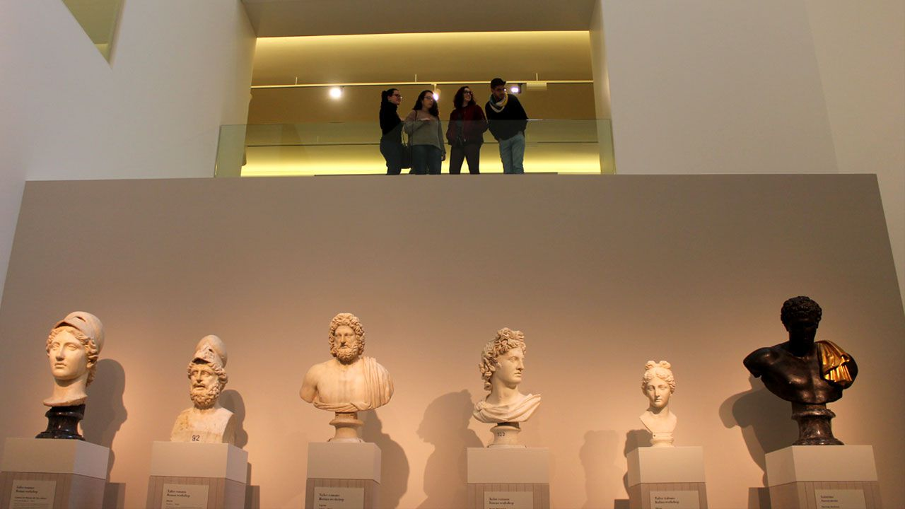 Visitantes del Bellas Artes sobre una serie de bustos con representaciones de dioses grecorromanos en la exposición 'Arte y Mito'