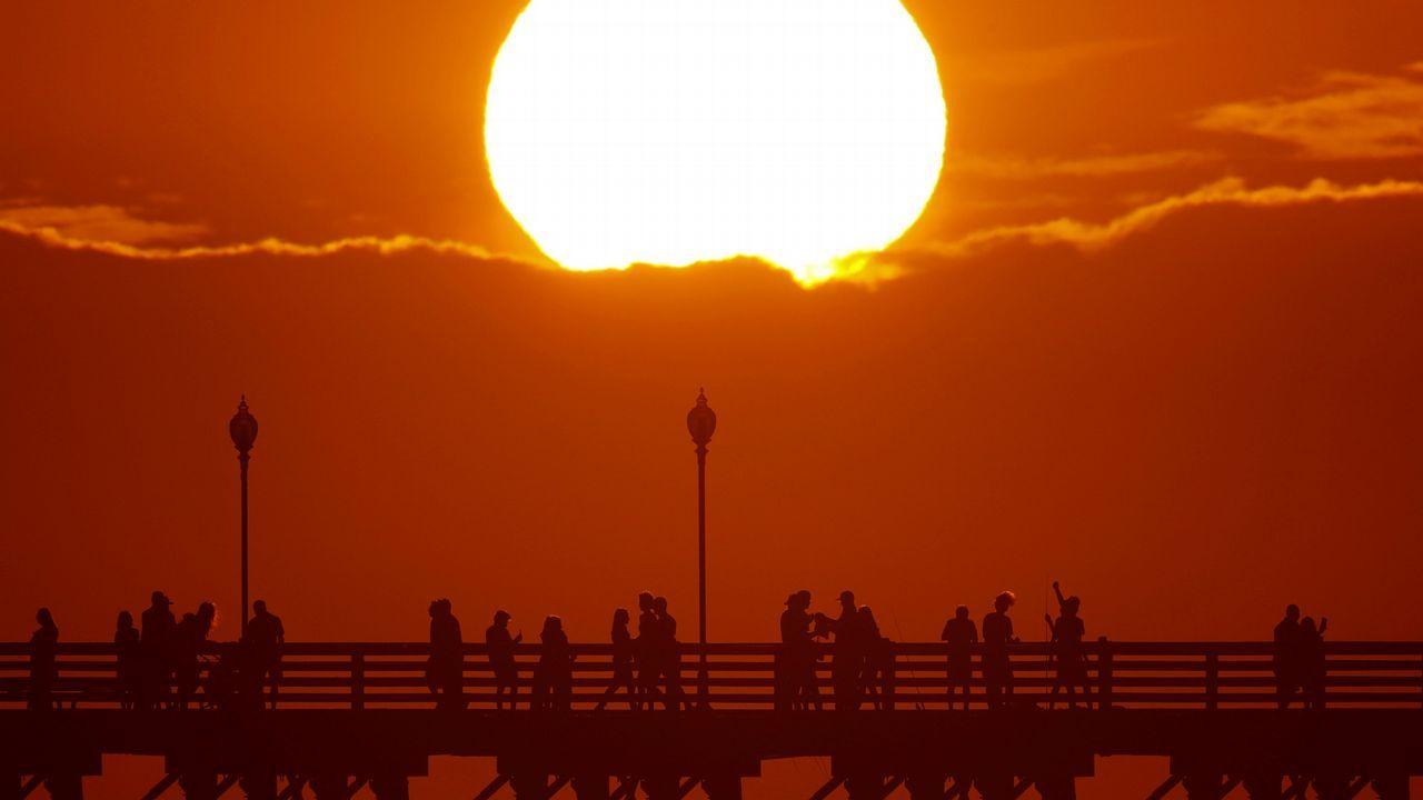 .El sol se pone detrás de una nube mientras la gente se refresca con un paseo a lo largo de un muelle oceánico en Oceanside, California