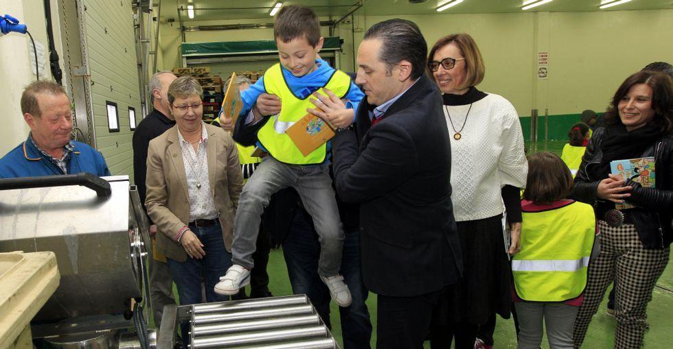 El gerente de ABSA, Miguel Neira, pesa a uno de los escolares durante la visita con la conselleira.