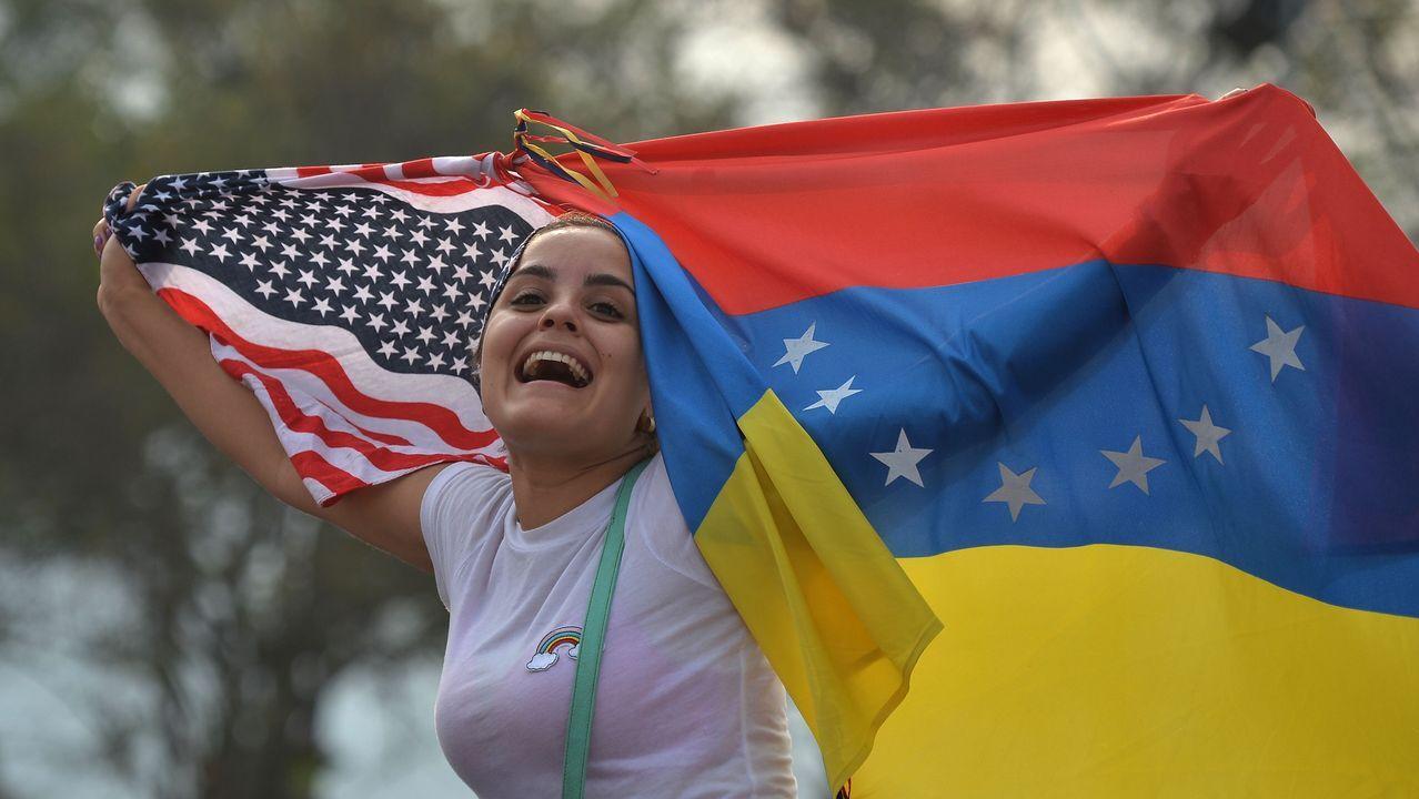 Una mujer ondea las banderas de Estados Unidos y Venezuela durante el concierto celebrado en el puente fronterizo de Tienditas, en Cúcuta (Colombia)