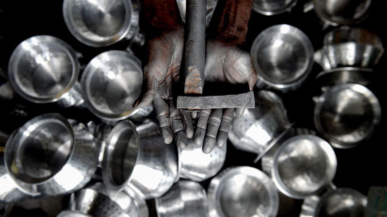 .Un trabajador indio con las manos manchadas de aluminio en un taller de utensilios