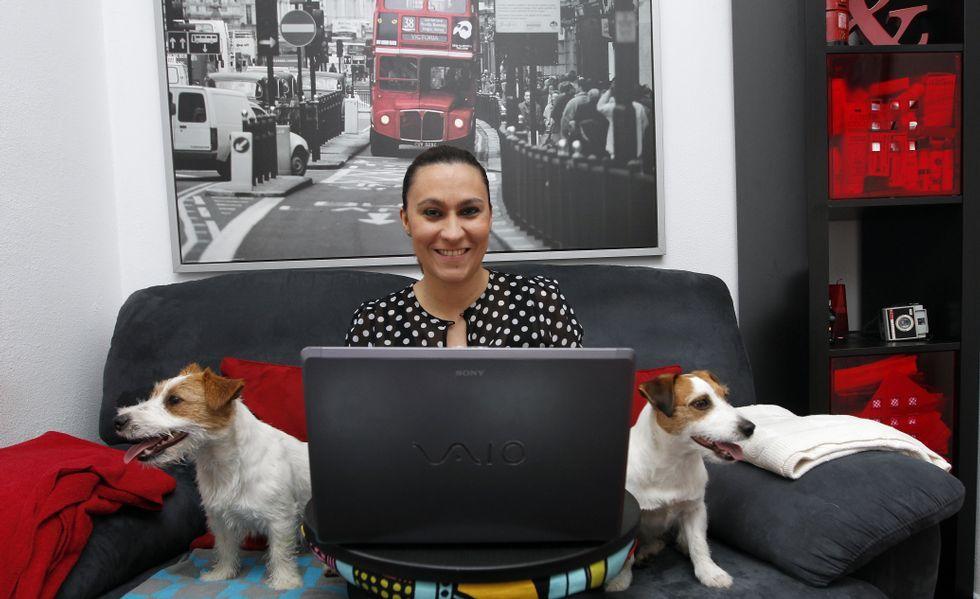 Marta, con sus perros Lucca a la derecha de la imagen y George, a la izquierda, con su herramienta de trabajo, el ordenador.