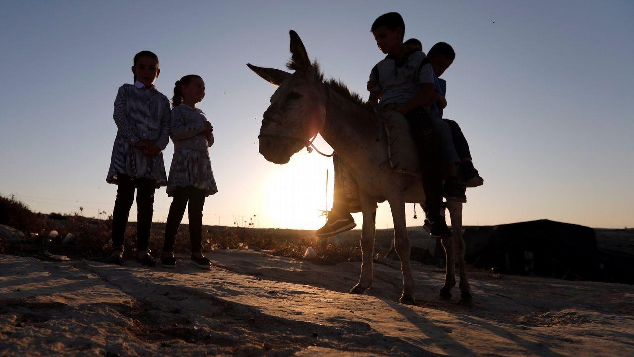 Varios niños palestinos se preparan para el primer día de colegio del nuevo curso, en la aldea de Sosia, al sur de Hebrón, Cisjordania, Palestina. Cerca de 300.000 escolares regresaron hoy al colegio en las escuelas de la agencia de la ONU para los refugiados palestinos (UNRWA) en la Franja de Gaza, pero lo hicieron sin material, con clases en tres turnos y con fondos asegurados para continuar la escolarización solo hasta finales de mes. Las escuelas también reabrieron hoy en Cisjordania y en Jerusalén Este, con lo que, junto a Gaza, un total de 1,3 millones de niños palestinos regresaron a las aulas en 3.030 escuelas, de las que 2.212 son públicas, 451 privadas y 377 de la UNRWA