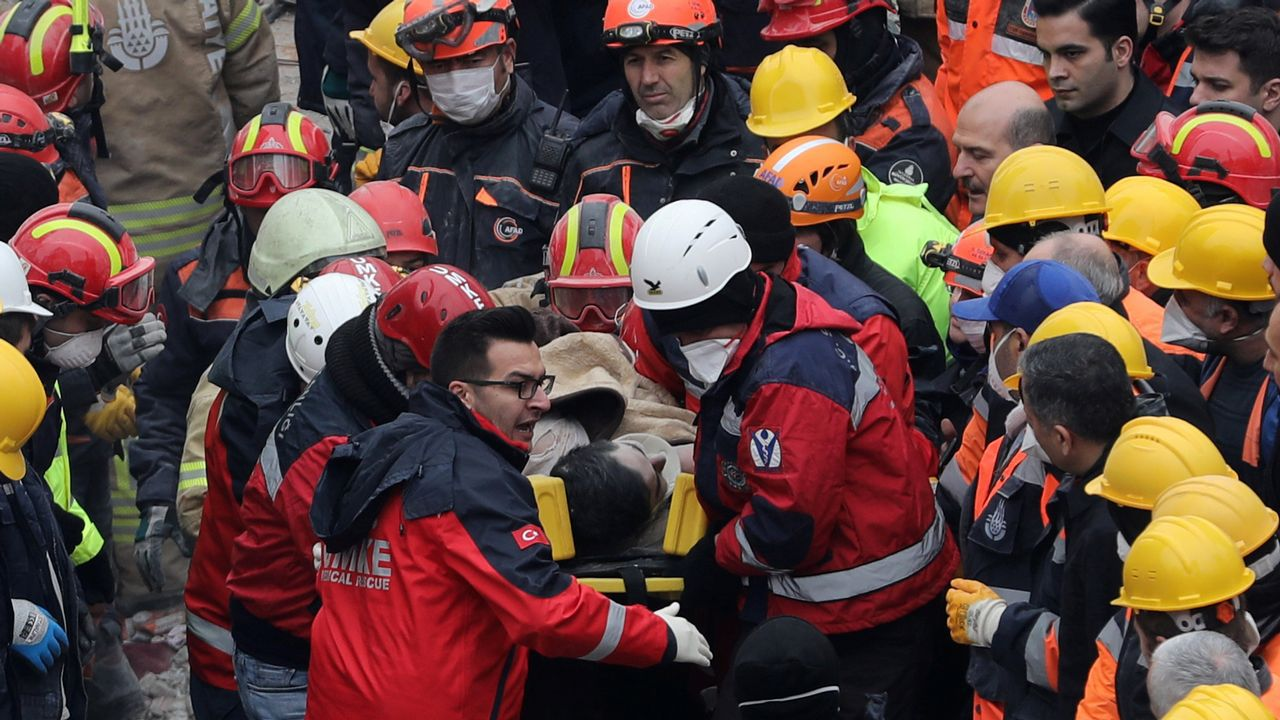 Un grupo de pasajeros consulta los vuelos en el Aeropuerto de Asturias.Miembros del dispositivo de rescate evacúan al joven de 16 años que sobrevivió 45 horas bajo los escombros del edificio de Estambul