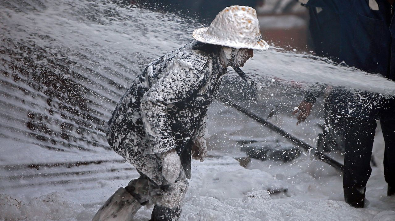 Un bombero, cubierto con espuma, intentando controlar un incendio en una fábrica india