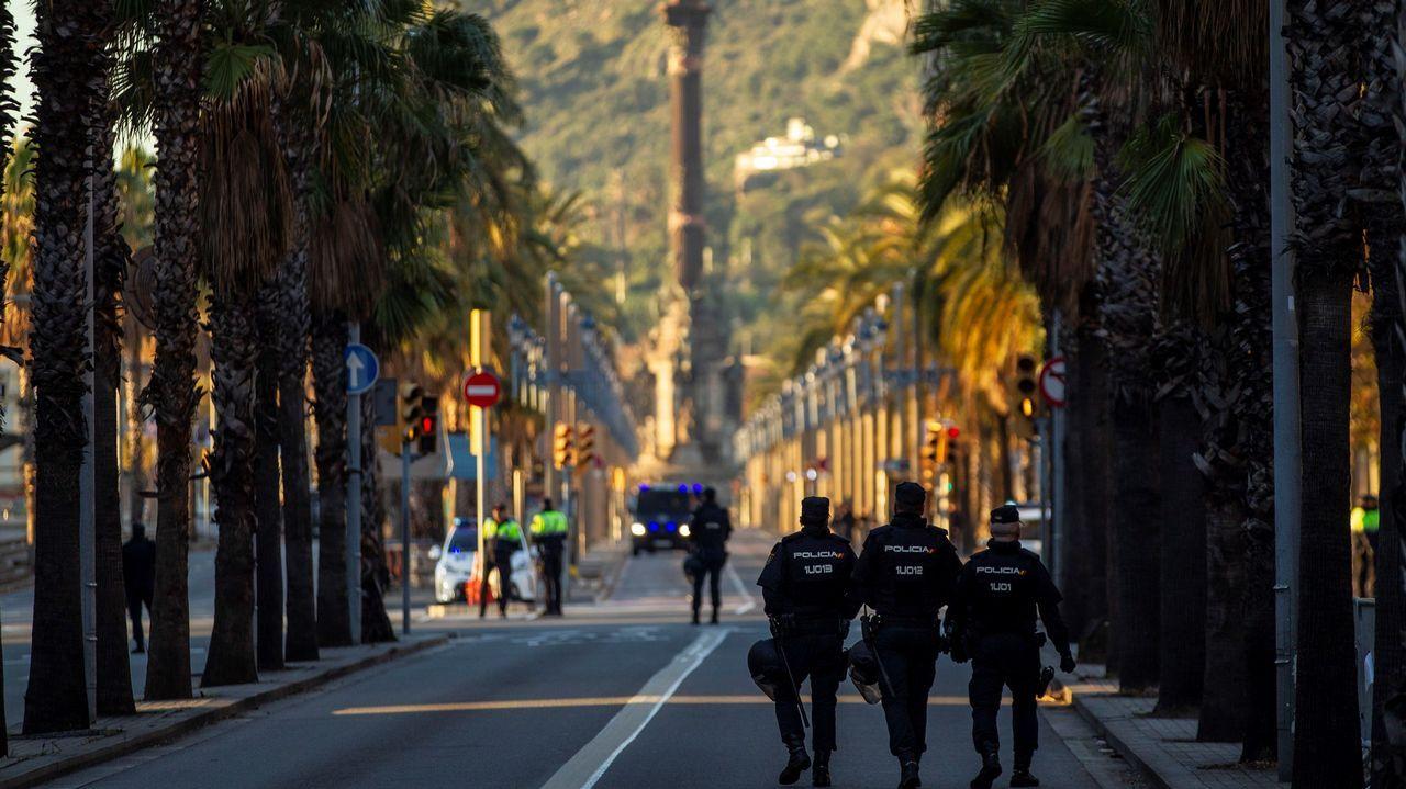 Miembros de las fuerzas de seguridad protegen el paseo de Colón, que aparece desierto, la zona más cercana a la Llotja de Mar de Barcelona