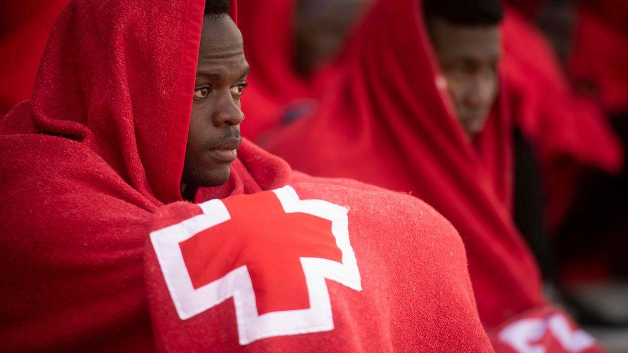 .Un hombre se abriga con una manta de Cruz Roja tras llegar en un barco de guardacostas al puerto de Tarifa