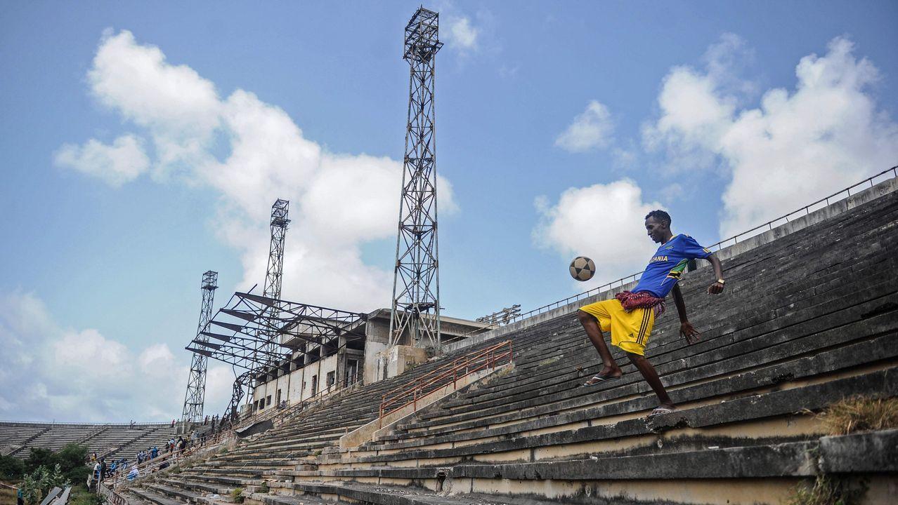 .Un niño somalí maneja un balón en el estadio de Mogadishu después de que la Misión de la Unión Africana en Somalia (AMISOM) abandonara el estadio en Mogadiscio, Somalia. El estadio de Mogadiscio se ha ocupado como base de la AMISOM desde 2011 volvió a ser el terreno público que solía ser