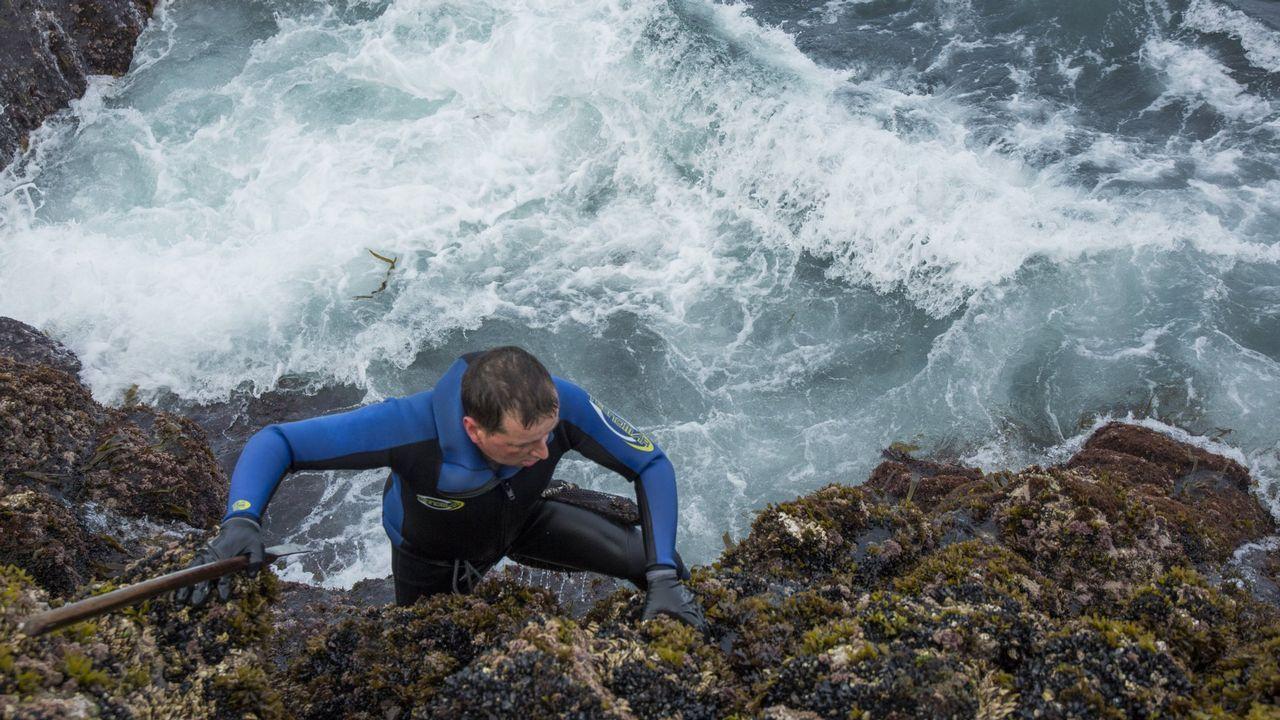 El pescador Juan Antonio González (i) posa con el primer salmón que se captura en la temporada de pesca de esta especie en los rios asturianos, el tradicional campanu