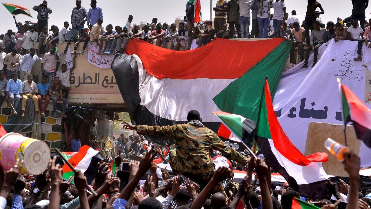 Los manifestantes llevan a hombros a un militar tras conocer el derrocamiento de Omar al Bashir