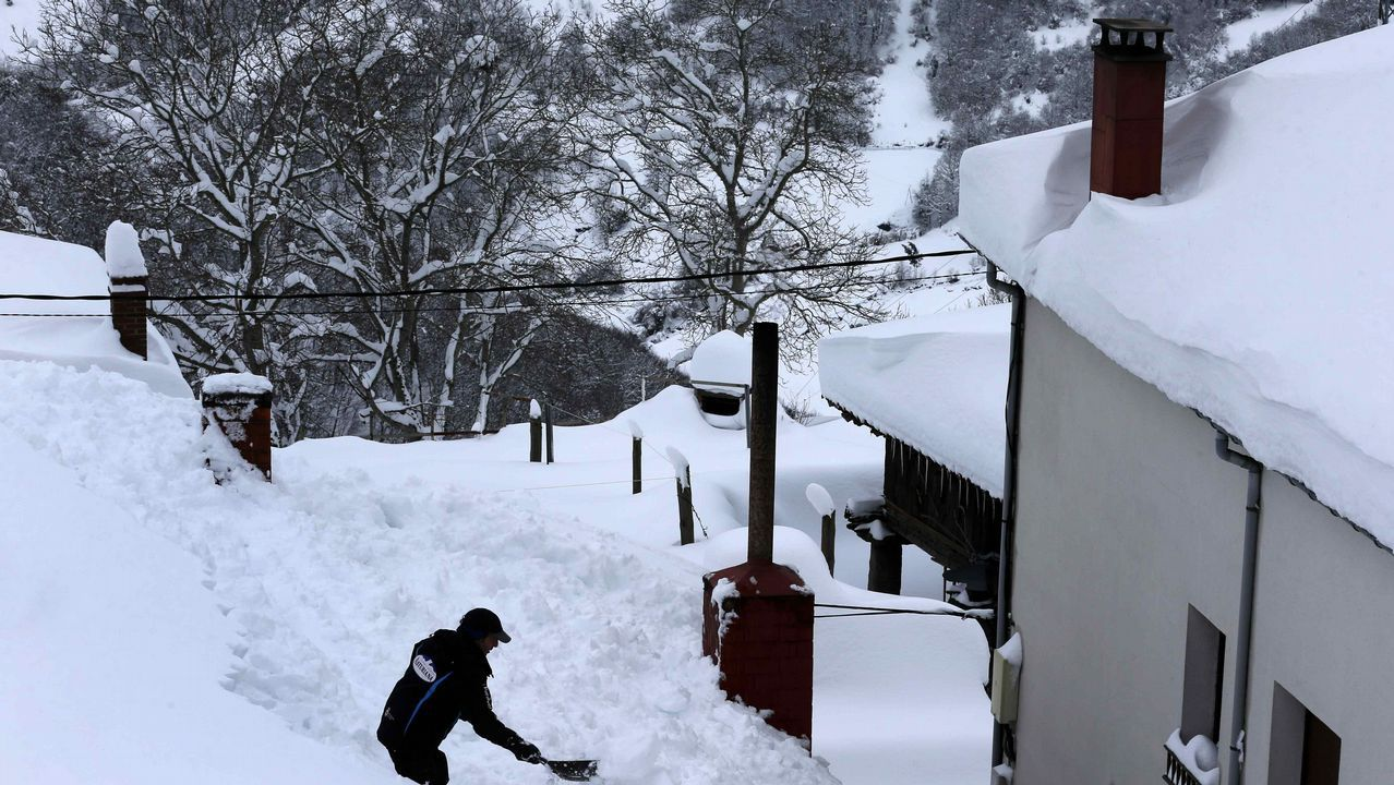 .Vecinos de Pajares (Asturias) retiran nieve del tejado de su casa de 300 años, una de las más antiguas del pueblo.